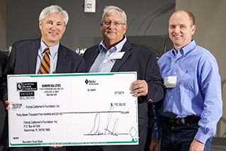 Photo of Dean Saunders, Jim Strickland, and Eric Jacobsen presenting donation check